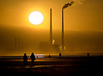 Source of solar energy, setting behind user of fossil fuel energy - sun setting behind Poolbeg Generating station, Ringsend Dublin, 28 December 2008. The Walkers are on Bull Island, in North Dublin. Poolbeg station burns a combination of oil and natural gas. Dubliners have a high carbon footprint, but could become more energy efficient and self-sufficient using sustainable energy sources. he energy generating power station is Ireland's second most polluting installation in terms of carbon dioxide, co2 emissions, according to the European Environment Agency.