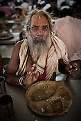 A Sadhu is seen eating the prasad at The Sai Prasadalaya in Shirdi, Maharashtra, India. The prasadalaya feeds an approximate number of 30000 Sai Baba devotees as a Prasad (holy meal). Free Prasad meals are served to all the devotees. An approximate number of 1000 devotees are served everyday with this facility. Expenses for a plate of Prasad meal  is around Rs. 15/- but the Saibaba Sansthan provides prasad meals to all Sai devotees to Rs. 6/- only. The prasadalaya at the Shirdi Sai Baba Shrine is powered by a large array of concave mirrors that transform sunlight to energy to create hot water and steam for the cooking process. Photograph: Sanjit Das