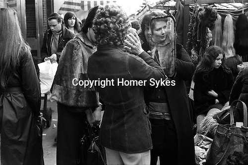 Woman trying on wig. Roman Road market, east London. England 1975