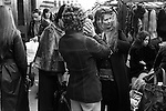 Woman trying on wig. Roman Road market, east London. England 1975