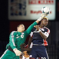 Toronto FC goalkeeper Joe Bendik (12) and New England Revolution forward Dimitry Imbongo (92) battle for the ball.  In a Major League Soccer (MLS) match, Toronto FC (white/red) defeated the New England Revolution (blue), 1-0, at Gillette Stadium on August 4, 2013.