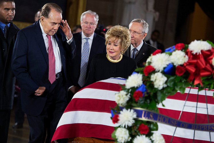 "UNITED STATES - DECEMBER 20:  Former Sen. Bob Dole, R-Kan., salutes the casket of the late Sen. Daniel Inouye, D-Hawaii, as his body lies in state in the Capitol rotunda, as Dole's wife, former Sen. Elizabeth Dole, R-N.C., looks on.  Bob Dole and Inouye knew each other since they were recovering from World War II battle wounds.  Dole was assisted to the casket saying ""I wouldn't want Danny to see me in a wheelchair.""  (Photo By Tom Williams/CQ Roll Call)"