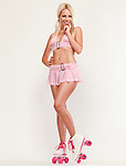 Glamorous pinup girl wearing a pink mini skirt and classic roller skates isolated on studio background