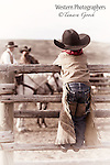 A photo of a little boy dressed in cowboy gear looking over a fence at two cowboys on horse back.