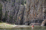 A canoe is dwarfed by the high rocky cliffs along the Dearborn River in western Montana