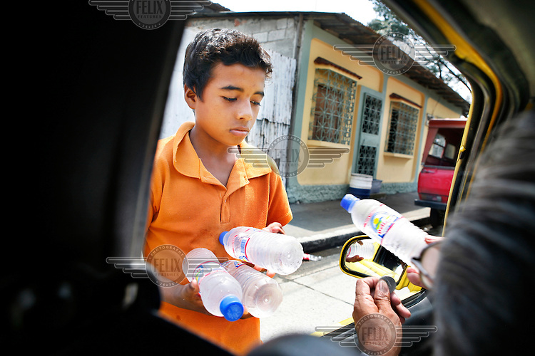 A boy sells water to passengers in a car.