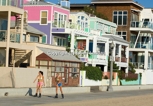 Rollerbladers skate past a section of beach front houses on the bike path just north of the Santa Monica Pier.