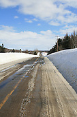 rural road in early spring, snow and ice accumulated during winter on asphalt road start to melt from warmer spring sun during the day