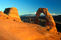 Sunset light on Delicate Arch sandstone rock formation below clear blue sky, Arches National Park, near Moab, Utah.