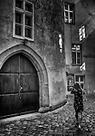 Woman walking in Prague around cobbled streets with sunlit walls