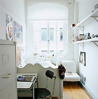 A child's bedroom with whitewashed exposed brick walls and a white wooden bed