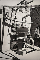 Hopi man weaving an indigo (a blue wool manta or woman's dress), in Oraibi, Arizona, with a blanket made from rabbit fur strips hanging on the wall on the right, an ancient technique found in Four Corners archaeological sites, photograph by Adam Clark Vroman, 1902, courtesy of the Los Angeles County Museum of Natural History, in the Anasazi Heritage Center, an archaeological museum of Native American pueblo and hunter-gatherer cultures, Dolores, Colorado, USA. Picture by Manuel Cohen