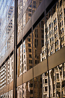 """Abstract reflection on the facade of a modern skyscraper. The architecture of Chicago has influenced and reflected the history of American architecture. The city of Chicago, Illinois features prominent buildings in a variety of styles by many important architects. Since most buildings within the downtown area were destroyed by the Great Chicago Fire in 1871, Chicago buildings are noted for their originality rather than their antiquity..Beginning in the early 1880s, architectural pioneers of the Chicago School explored steel-frame construction and, in the 1890s, the use of large areas of plate glass. These were among the first modern skyscrapers and amongst their most famous architects were William LeBaron, John Wellborn Root Sr., Daniel Burnham and Charles Atwood. Louis Sullivan was perhaps the city's most philosophical architect. Realizing that the skyscraper represented a new form of architecture, he discarded historical precedent and designed buildings that emphasized their vertical nature. This new form of architecture, by Jenney, Burnham, Sullivan, and others, became known as the """"Commercial Style,"""" but it was called the """"Chicago School"""" by later historians..Since 1963, a """"Second Chicago School"""" emerged, largely due to the ideas of structural engineer Fazlur Khan. Some of Chicago's skyscrapers such as the John Hancock Center, Willis Tower (formerly known as the Sears Tower) and The Trump International Hotel and Tower are amongst the tallest buildings in the world."""