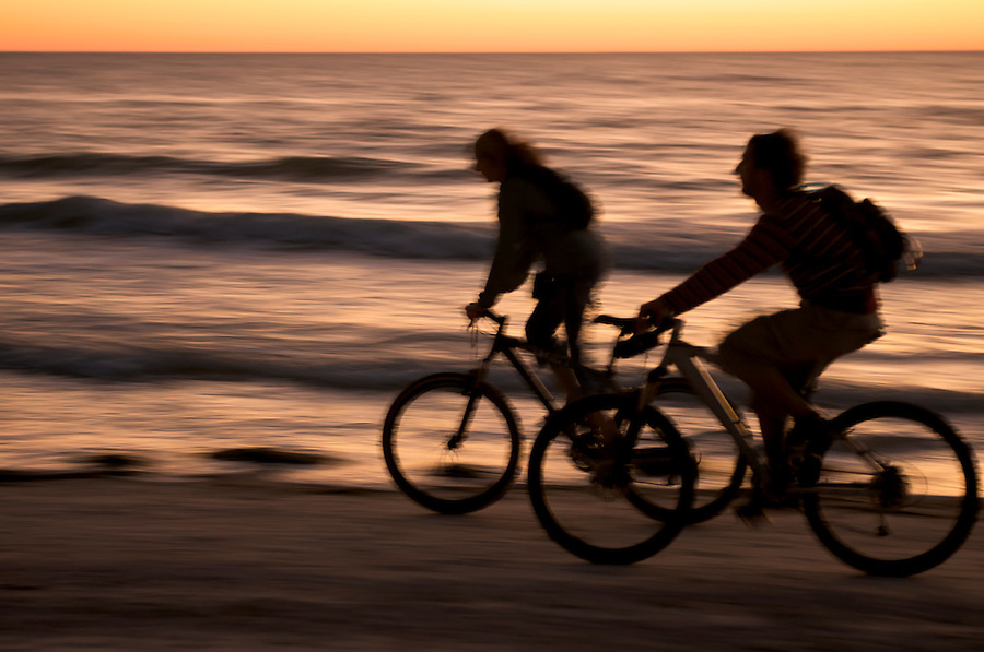 Couple ryding bycicle at sunset in Honeymoon Island, Florida.