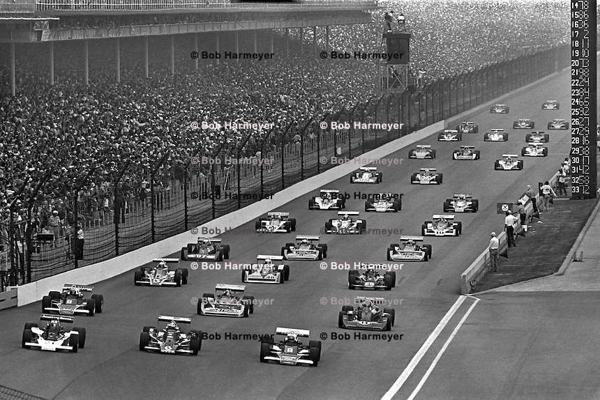 INDIANAPOLIS, IN - MAY 29: The field drives down the frontstretch on a parade lap prior to the Indianapolis 500 on May 29, 1977, at the Indianapolis Motor Speedway in Indianapolis, Indiana.
