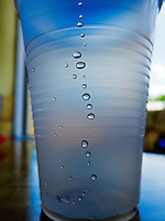 Backlit water droplets on the inside of a plastic drinking cup on a fast-food restaurant table.