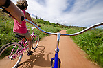 Woman bicycling along a bike path along the coast in Kapa'a, Kauai, Hawaii