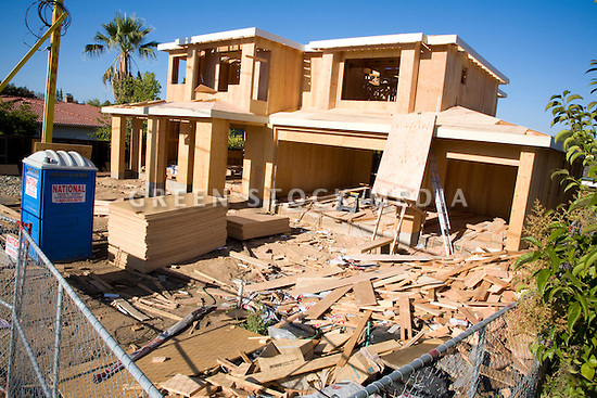 Wooden two story house under construction green stock media for How to get a land loan to build a house