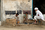 A father and son work together in their streetside shoe repair business as a customer waits.