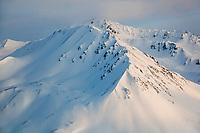 Sunset light on the snow covered mountain peaks of the eastern Alaska Range mountains.