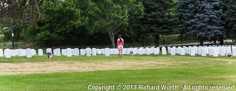 A visitor among the marble headstones at Fort Logan National Cemetery, Denver, Colorado