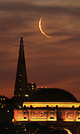A small crescent moon rose over the city nearly at the same time as morning twilight appeared.