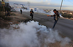 A Palestinian protester runs from tear gas fired by Israeli soldiers during a protest against Israel's plan of forced relocation for Bedouin residents in the southern Negev, outside the Beit El settlement near the West Bank city of Ramallah November 30, 2013.  Photo by Issam Rimawi