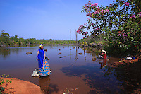 A woman in sumptuous Fulani costume takes her laundry to the pond in the heart of the gallery forest.
