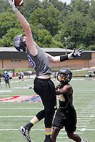NWA Democrat-Gazette/DAVID GOTTSCHALK - Fayetteville High School's Drake Wymer catches a touchdown pass between Midwest City High School defenders Friday, July 10, 2015 during the Southwest Elite 7 on 7 tournament at Fayetteville High School.