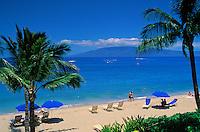 Sunbathing on Kaanapali beach, west coast Maui, with view of the island of Lanai