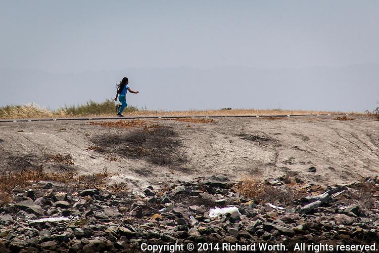 A young girl joyfully runs along the par course path at the San Leandro Marina Park.