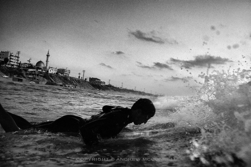 Mahmoud Alyrashi paddles out through the waves on edge of Gaza City, Gaza Strip. Leaving Gaza has become extremely difficult since the Israeli blockade began in 2007.
