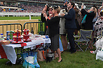 Royal Ascot horse racing Berkshire. 2016. Heath side of racecourse, a group of friends from near Wolverhampton on an away day break with picnic table and food watch the racing. This is an annual event.