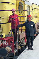 Staff members for the Palace on Wheels train posing with the train, Udaipur, India.