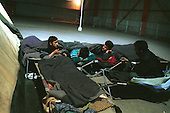 Iraqi-Kurdish asylum seekers inside the Red Cross refugee camp in Sangatte. They make nightly attempts to cross the English Channel to Dover from the camp. ..Picture taken April 2002 in Sangatte by Justin Jin. Copyright 2002 by Justin Jin.