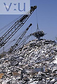 A large electromagnet lifting pieces of scrap metal.