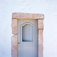 A contemporary door within a rustic frame set into a whitewashed wall