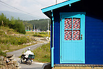 A motorbike passes one of the rainbow-colored cabins at The Cicada Fort that stands on the tsunami-ravaged land of Takata district in Rikuzentakata, Iwate Prefecture Japan on 08 Oct. , 2013. PHOTO: ROB GILHOOLY