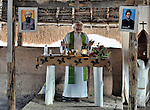 Father Mario Benedetti, a Comboni father from Italy, celebrates Mass in the Makpandu refugee camp in Southern Sudan, 44 km north of Yambio, where more that 4,000 people took refuge in late 2008 when the Lord's Resistance Army attacked their communities inside the Democratic Republic of the Congo. Above the altar are images of Saint Daniel Comboni and Saint Josephine Bakhita. Attacks by the LRA inside Southern Sudan and in the neighboring DRC and Central African Republic have displaced tens of thousands of people, and many worry the attacks will increase as the government in Khartoum uses the LRA to destabilize Southern Sudan, where people are scheduled to vote on independence in January 2011. Father Benedetti and other Catholic pastoral workers have accompanied the people of this camp from the beginning. NOTE: In July 2011 Southern Sudan became the independent country of South Sudan.