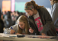 """NWA Democrat-Gazette/J.T. WAMPLER Sydney Cinnamon (left) and Hannah Martin sign a banner Monday Feb. 13, 2017 at Rogers Heritage High School. The banner reads: """"Heritage United: We are one, divided by none."""" Students were encouraged to sign their name and add a message on what unites them as opposed to what divides them."""