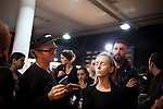 A model sits during a demo surrounded by make-up artists, backstage for the Brazilian brand, Triton, at São Paulo Fashion Week for Summer Season 2013/2014, at Bienal, in São Paulo, Brazil, on Wednesday, March 20, 2013.
