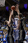 30 November 2014: Duke's Jahlil Okafor (center) shoots between Army's Larry Toomey (left) and Tanner Plomb (right). The Duke University Blue Devils hosted the West Point Military Academy Army Black Knights at Cameron Indoor Stadium in Durham, North Carolina in a 2014-16 NCAA Men's Basketball Division I game. Duke won the game 93-73.
