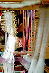 A woman weaving traditional silk cloth under her home in Phonsavan, Xieng Khuang,Laos.