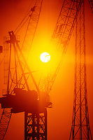 00252IAS..Construction tower cranes sunset silhouette....construction crane tower silhouette orange sky sun sunset strength power powerful building equipment....