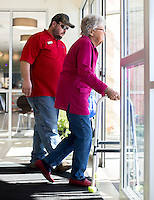 NWA Democrat-Gazette/JASON IVESTER --01/26/2015--<br /> Richard Embry with Hope Cancer Resources helps patient Rowena Smith out to his vehicle on Monday Jan. 26, 2015, at the Highlands Oncology Center in Rogers. Embry was transporting Smith to her Holiday Island home following treatment at the center.
