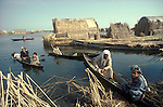 Marsh Arabs. Southern Iraq. Circa 1985. Marsh Arab men. Children and fathers in boats. Reed building on small artificial island called a kibasha. Permanent island called a dibin.