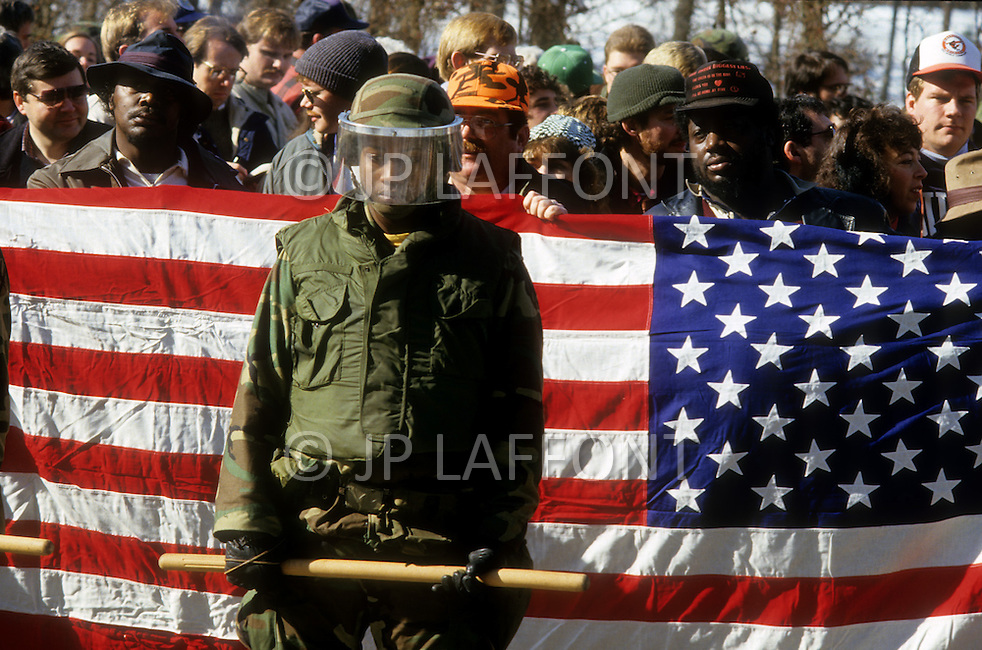 Forsyth County, Cumming, GA. January 24th, 1987. <br /> A young black american military man stands in front of the American Flag being held by protestors, at a civil rights march attended by 20,000 integrationists, including civil rights leaders, U.S. senators and other senior officials. They were met again by about counter-protesters led by The Nationalist Movement.