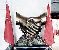 A trophy of people shaking hands above the Great Wall of China between national flags.