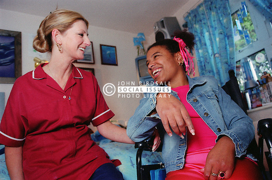 Care manager and young woman with Cerebral Palsy sitting together laughing in residential care centre,