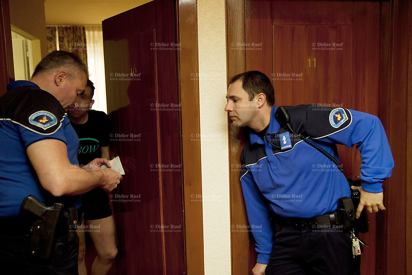 Switzerland. Geneva. Paquis neighborhood. Two police officers check the identity of an hotel guest.The policemen will ask the man to pay back an old fine and then he will be left free. 27.03.12 © 2012 Didier Ruef..
